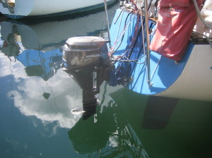four stroke outboard is fully deployed on stern of sailboat